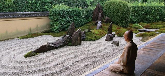 Monk Meditating by Zen Rock Garden