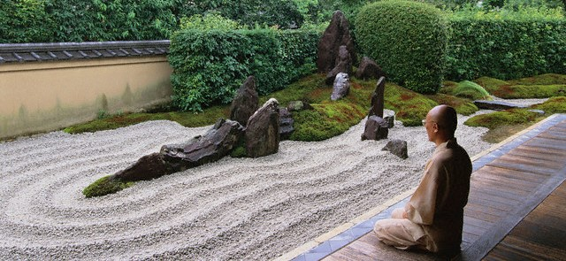 Monk Meditating by Zen Rock Garden